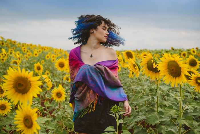 photo of standing woman flipping her hair in the middle of sunflower field
